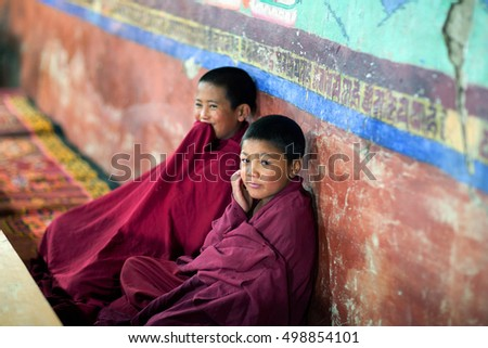 LADAKH, INDIA - JUNE 11, 2012: Two young Buddhist monks praying in Thiksey gompa during Puja ceremony.