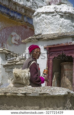 Ladakhi woman in traditional clothing waiting to make her morning round of the prayer wheels at Lamayuru Monastery CIRCA 2015