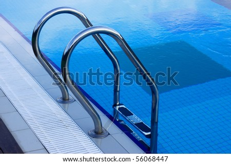 Ladder and pool edge Metal ladder to swimming pool with blue water - stock photo