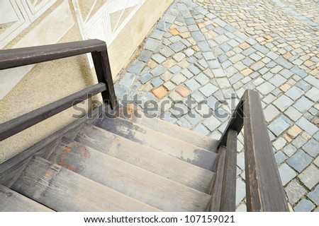 ladder and railing connected to an old pavement - stock photo