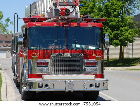 ladder firetruck on the side of a city street - stock photo