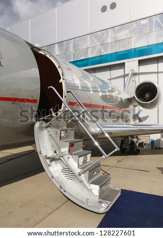ladder in a private jet and hangar - stock photo