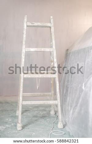 ladder in an empty room covered in dust sheets prepared for painting and renovation