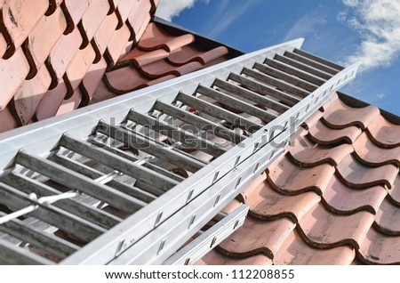 Ladder on a house roof - stock photo