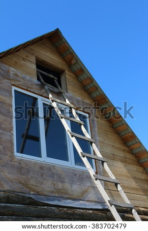 Ladder to the attic of a village log house under construction against a blue sky