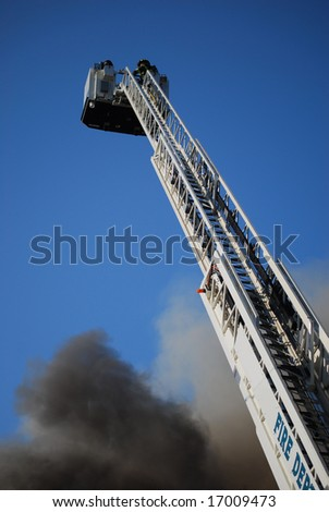 Ladder truck with fireman at top battles a blaze. - stock photo