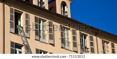 Ladder used to move furniture with elegant palace in background - stock photo
