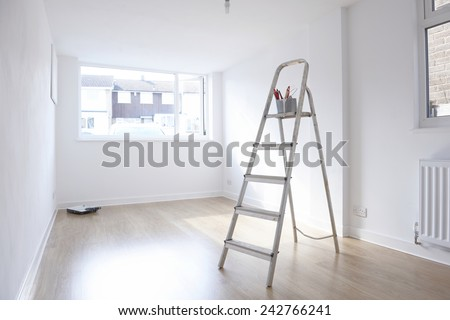 ladder with paint pot and brushes standing in empty room - stock photo