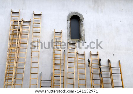 Ladders leaning against the wall of a church - stock photo
