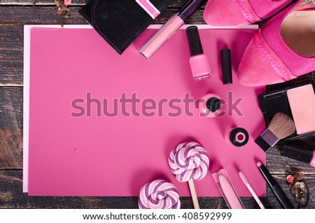 Ladies background - shoes, lipstick, nail polish, earrings, blush, lollipops on pink paper and wooden background.  Top view
