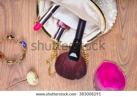 Ladies Bag for cosmetics with brushes, pink lipstick, nail polish, bracelet and dry flower on the brown wooden table. The concept of beauty and personal care - stock photo
