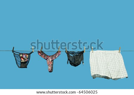 Ladies lingerie  lingerie beside  a pair of mens boxer shorts hanging on a clothesline against a brilliant blue sky with copy space.. - stock photo