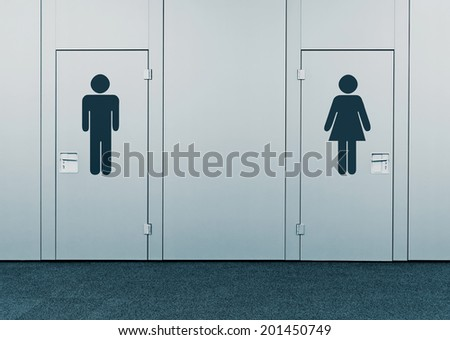 Ladies room and mens room. Closed toilet doors with printed marks. - stock photo