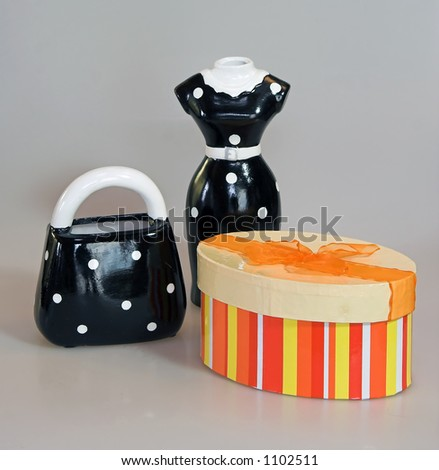 ladies shopping metaphors including brightly colored gift or pill box, dress and purse. - stock photo