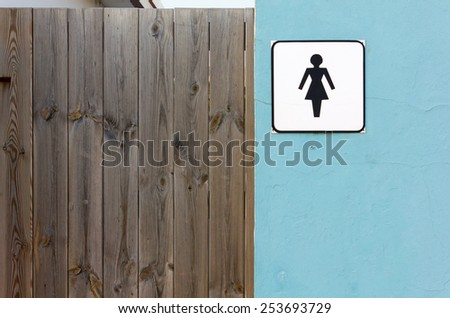 Ladies Toilet Sign on an Exterior Wall next to a Wooden Door - stock photo