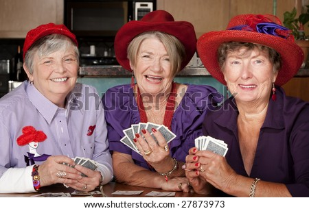 Ladies wearing red hats playing a hand of cards
