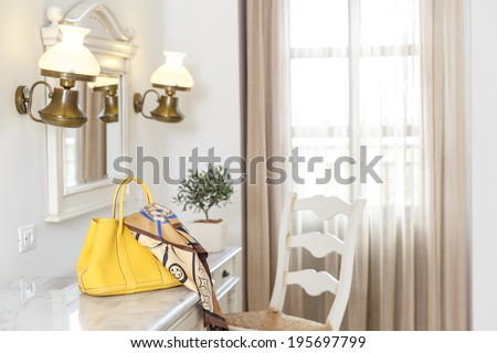 Ladies yellow handbag and scarf on a side table below a wall mirror and lights with an empty white wooden ladder back chair in front of a window - stock photo