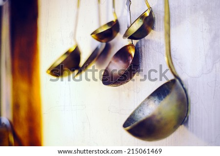 Ladles hanging on a white wall - stock photo