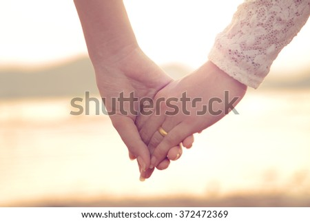 Lady and lady holding hands together with love and care in sunset scene - stock photo
