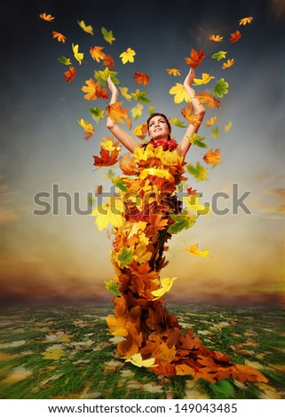 Lady Autumn in falling golden leaves dress - stock photo
