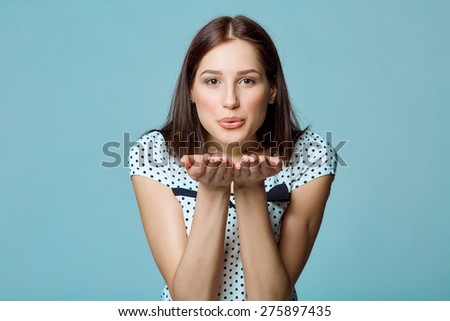 Lady beautiful woman blowing a kiss at you against blue background - stock photo
