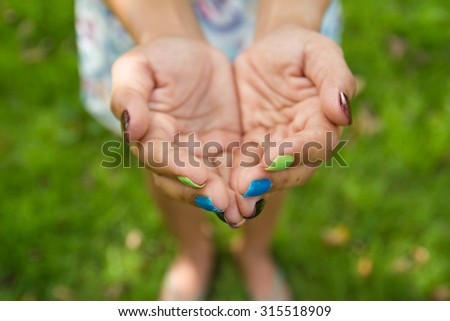 lady beg something with colorful nails, heart like shape of hands