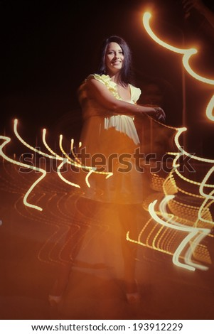 Lady dancing in the dark with lightpainting, long time exposure - stock photo