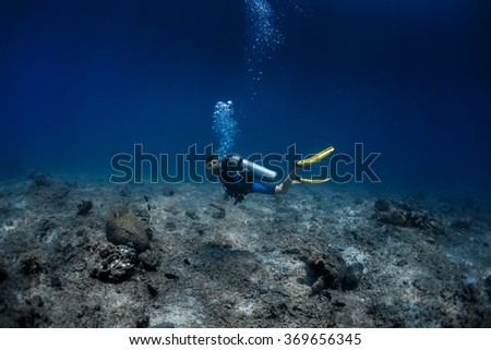 Lady diver swimming underwater over the sea desert, over the coral reef's remains - stock photo