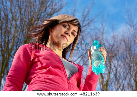 Lady drinking water in a forest. View from below. - stock photo