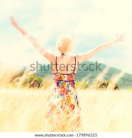 Lady enjoying the nature. Young woman arms raised enjoying the fresh air in summer meadow. Instagram style retro shot. - stock photo