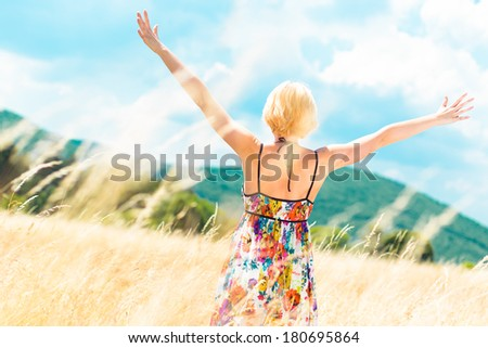 Lady enjoying the nature. Young woman arms raised enjoying the fresh air in summer meadow.