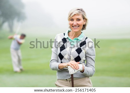 Lady golfer smiling at camera with partner behind on a foggy day at the golf course - stock photo