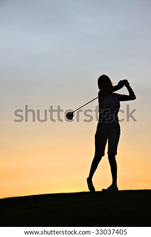 Lady golfer swinging her driver at sunrise. - stock photo