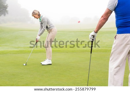 Lady golfer teeing off for the day watched by partner on a foggy day at the golf course - stock photo