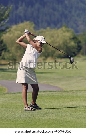 Lady golfer tees off with a driver - stock photo