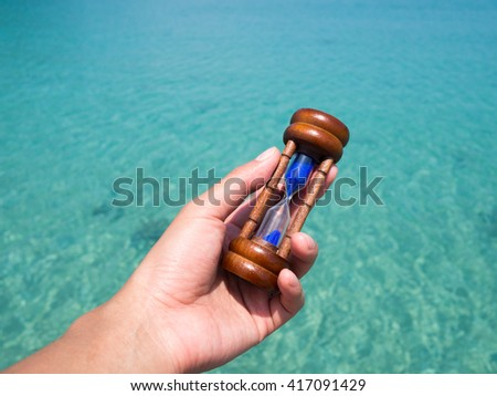 lady hand holding hourglass, sandglass against with green blue sea water surface in background. Time to vacation, holiday, summer concept. Slow life concept. - stock photo
