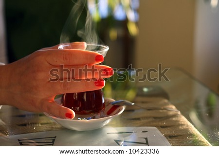 lady hand with a glass of turkish tea - stock photo