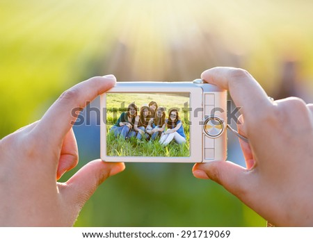 Lady hands taking photo of a young group of friends sitting on grass outdoors.