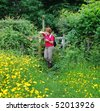 Lady Hiker leaning on a fence in a field of Buttercups reading a map - stock photo
