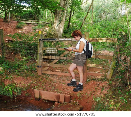 Lady Hiker leaning on a fence in a woodland glade reading a map