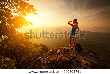 Lady hiker on top of the mountain during sunrise - stock photo