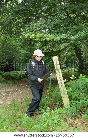 Lady Hiker reading a Map standing next to a Footpath sign on an english woodland track in the rain. - stock photo