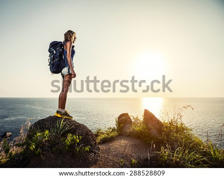 Lady hiker standing on the rock and enjoying sunset over sea
