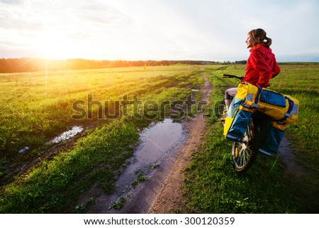 Lady hiker standing on the wet road with loaded bicycle - stock photo