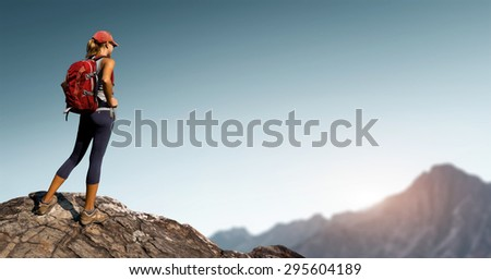 Lady hiker standing on top of the hill with clear sky and mountains on the background - stock photo
