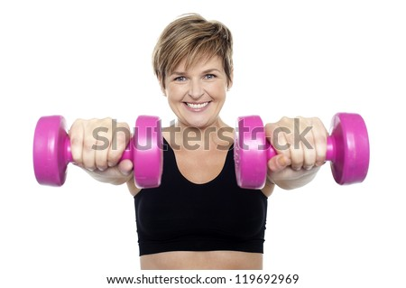 Lady holding pink dumbbells. Arms outstretched. Isolated over white - stock photo