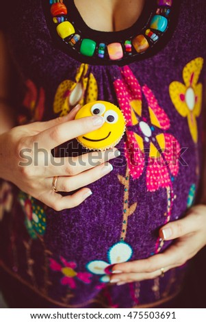 Lady holds a cupcake with yellow face on her beautiful pregnant belly