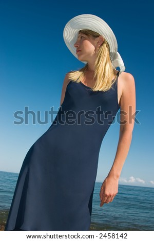 Lady in a dark blue dress and a hat - stock photo
