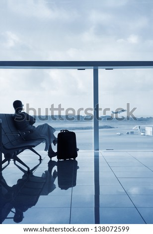 Lady in a lobby airport waiting for her flight, looking through a glass with solar protection. - stock photo