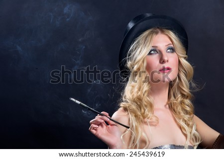 Lady in Black Hat smokes a long slim cigarette - stock photo
